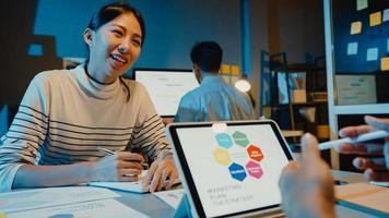 asien affärsmän möte plan analys statistik brainstorm och huvudet av teamet hålla tablett punkt graf diagram och anställd notera i moderna hemmakontor natt. finansstrategi framgång koncept. foto