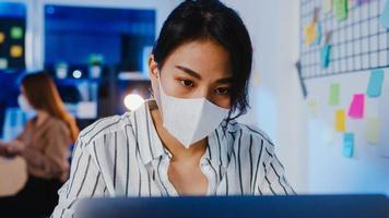 glad asiatisk affärskvinna som bär medicinsk ansiktsmask för social distansering i en ny normal situation för att förebygga virus medan du använder en bärbar dator tillbaka på jobbet på kontorsnatten. liv och arbete efter coronaviruset. foto