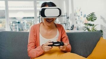 asiatisk dam bär headsetglasögon av virtuell verklighet spela joystick -spel på soffan i vardagsrummet hemma. stanna hemma covid karantän, tänk om verkligheten, vr hemma, vr teknik för framtida koncept. foto