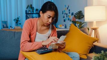 asiatisk dam känner sig stressad och orolig med räkning och faktura kreditkort beräknar lån på soffan hemma. bostadslån stress, få lån inget jobb, coronavirus svårigheter lån, kan inte göra lån betalning koncept. foto