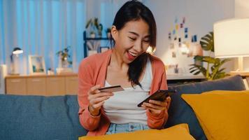 natt vacker leende asiatisk dam använda mobiltelefon beställa online shopping produkt med kreditkort på soffan i vardagsrummet. stanna hemma, självkarantänaktivitet, rolig aktivitet för covid -karantän. foto