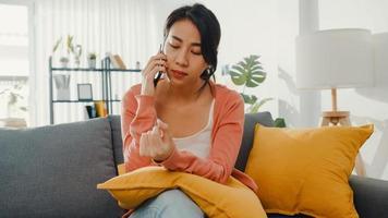 ung dam som sitter i soffan prata med en vän och få dåliga nyheter hemma. långdistansförhållande, dåligt förhållande, arbetsproblem, trasigt förhållande, håll avstånd, covid karantänbegrepp. foto
