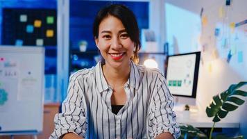 porträtt av vacker verkställande affärskvinna smart vardagskläder som tittar på kameran och ler, glad i modern kontorsarbetsplats natt. ung asiatisk dam prata med kollega i videosamtalsmöte hemma. foto