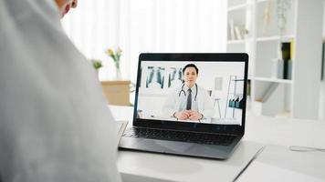 ung asiatisk damläkare i vit medicinsk uniform med bärbar dator som talar videokonferenssamtal med överläkare vid skrivbordet på vårdkliniken eller sjukhuset. social distansering, karantän för corona. foto