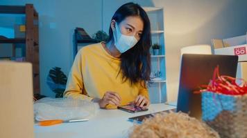 ung asiatisk affärskvinna bär ansiktsmask kontrollera inköpsorder på smartphone och lager i dator på hemmakontor på natten. småföretagare, onlinemarknadsleverans, livsstil frilansande koncept. foto
