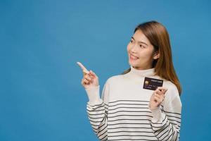 ung asiatisk dam visar kreditbankkort med positivt uttryck, ler brett, klädd i vardagskläder som känner lycka och står isolerad på blå bakgrund. ansiktsuttryck koncept. foto