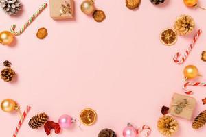 minimal kreativ lägenhet av julens traditionella komposition och nyårshelger. ovanifrån vinter juldekorationer på rosa bakgrund med tomt utrymme för text. kopiera rymdfotografering. foto