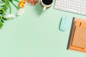 minimalt arbetsutrymme - kreativt plattläggningsfoto av arbetsytans skrivbord. ovanifrån kontorsbord med tangentbord, mus och anteckningsbok på pastellgrön bakgrund. ovanifrån med kopieringsutrymme, plattfotografering. foto