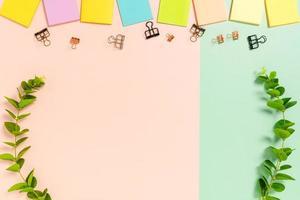 minimalt arbetsutrymme - kreativt plattläggningsfoto av arbetsytans skrivbord. ovanifrån kontorsbord med självhäftande anteckning på pastellgrön rosa bakgrund. ovanifrån med kopieringsutrymme, plattfotografering. foto