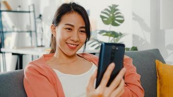 vacker asiatisk dam som ler och sitter på soffsamtal telefonsamtal säga hej med familjen hemma. stanna hemma, långdistansförhållande, familjeförhållande, hålla avstånd, covid karantänbegrepp. foto