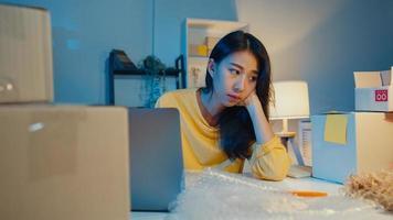 ung asiatisk affärskvinna tittar runt i rummet fullt av produktsaker och paketlåda känner sig stressad och upprörd med dålig försäljning på hemmakontoret på natten. småföretagare, online marknadsföringskoncept. foto