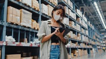unga asiatiska affärskvinnans chef bär ansiktsmask som letar efter varor med hjälp av digital surfplatta och kontrollerar lagernivåer i detaljhandelscentret. distribution, logistik, paket redo för leverans. foto