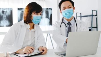 medicinskt team i asien allvarlig manlig och ung kvinnlig läkare med skyddande ansiktsmasker som diskuterar datortomografi resulterar på sjukhuskontor. social distans, livsstil ny normal efter corona -virus. foto