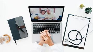 ovanifrån av ung asiatisk kvinnlig läkare i medicinsk uniform med stetoskop som använder bärbar dator som pratar videokonferenssamtal med patienten vid skrivbordet på vårdkliniken eller sjukhuset. konsult- och terapikoncept. foto