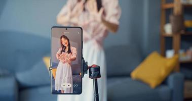 glad ung asiatisk tjejbloggare framför telefonkameran spela in video njuta av dansinnehåll i vardagsrummet hemma. socialt avstånd coronavirus pandemi koncept. frihet och aktiv livsstilskoncept foto