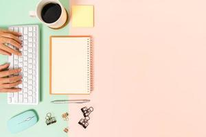kreativt plattläggningsfoto av skrivbordet på arbetsytan. ovanifrån kontorsbord med tangentbord, mus och öppen mockup svart anteckningsbok på pastellgrön rosa färgbakgrund. ovanifrån håna med kopia utrymme fotografering. foto