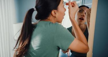 vacker asiatisk dam med avslappnad trasa satte mascara på ögonfransarna framför spegeln i sovrummet hemma på morgonen innan du går ut utanför. leende ung kvinna som sminkar sig och tittar på spegeln. foto