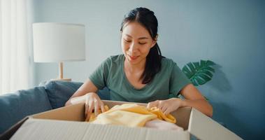 happy asia lady open kartongpaket spännande och njut av att försöka matcha med kvalitet på mode tygprodukt från onlinemarknaden i vardagsrummet hemma. online shopping och leverans koncept. foto