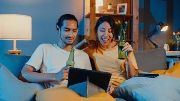 glada unga asiatiska par njuta av nattfest event online sitta soffa använda surfplatta videosamtal med vänner toast dricka öl via videosamtal online i vardagsrummet hemma, social distansering koncept. foto