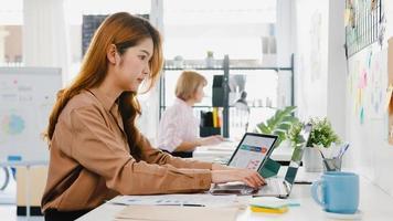 ung asiatisk affärskvinna entreprenör social distansering i en ny normal situation för att förebygga virus medan du använder bärbar dator och surfplatta tillbaka på jobbet på kontoret. livsstil efter coronaviruset. foto