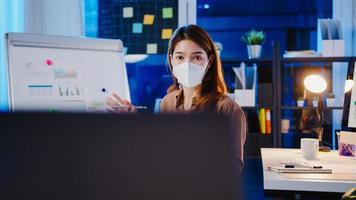 asiatisk affärskvinna bär ansiktsmask för social distansering i ny normal för virusförebyggande presentation till kollega om plan i videosamtal medan du arbetar på kontorsnatt. livsstil efter coronaviruset. foto
