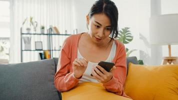 vacker dam som använder smartphone -chatt med par som sitter på soffan i vardagsrummet hemma på morgonen. stanna hemma, karantän för covid, nomofobi, onlineshopping, koncept för missbruk av sociala nätverk. foto