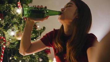 ung Asien kvinnlig dricka öl ha kul glad natt fest videosamtal samtal med par, julgran dekorerad med prydnader i vardagsrummet hemma. julkväll och nyårsfest. foto