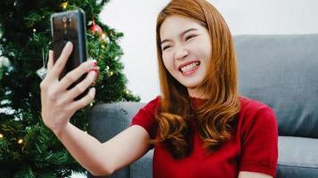 ung asiatisk kvinna som använder smarta telefonsamtal och pratar med par med julklappslåda, julgran dekorerad med prydnad i vardagsrummet hemma. jul- och nyårsfest. foto