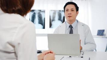 allvarlig asiatisk manlig läkare i vit medicinsk uniform som använder dator laptop levererar bra nyheter prata diskutera resultat eller symptom med kvinnlig patient sitta vid skrivbordet på vårdkliniken eller sjukhuskontoret. foto