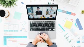 ovanifrån av ung asiatisk affärskvinna som använder bärbar dator prata med kollega om plan i videosamtalsmöte medan du arbetar hemifrån i vardagsrummet. social distansering, karantän för förebyggande av corona -virus. foto