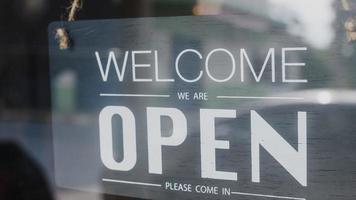 Välkommen, vi är öppna vintage svartvita retro -skyltar på ett kaffeglasdörrkafé efter karantän. ägare småföretag, mat och dryck, företag öppnar igen koncept. foto
