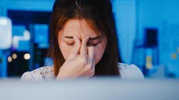 frilansande asiatiska kvinnor som använder laptop hårt arbete på nya vanliga hemmakontor. arbeta från huset överbelastning på natten, distansarbete, självisolering, social distansering, karantän för förebyggande av corona -virus. foto