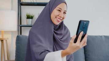 asien muslimsk dam bär hijab med telefonsamtal och pratar med par hemma. ung tonåring som gör vloggvideo till sociala medier på soffan i vardagsrummet. social distansering, karantän för corona. foto
