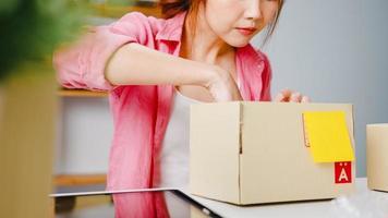 ung asien entreprenör affärskvinna förpackning produkt i kartong leverera till kund, arbetar på hemmakontor. småföretagare, starta online marknadsföring, livsstil frilans koncept. foto