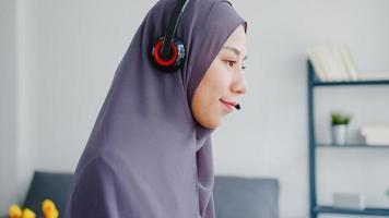 asien muslimsk dam bära hörlurar titta på webinar lyssna online kurs kommunicera genom konferens videosamtal hemma. distansarbete hemifrån, social distansering, karantän för förebyggande av corona -virus. foto