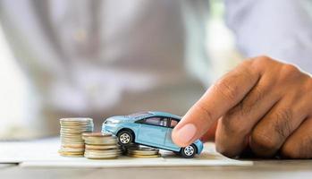 koncept för att spara pengar. bil, hus, myntbunt. foto