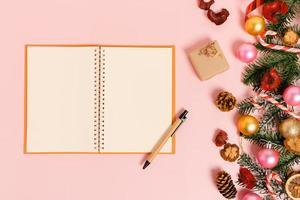 minimal kreativ lägenhet av vinterjulens traditionella komposition och nyårshelger. ovanifrån öppen mockup svart anteckningsbok för text på rosa bakgrund. håna och kopiera rymdfotografering. foto