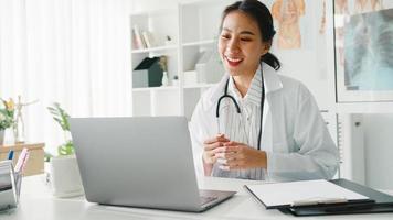 ung asiatisk damläkare i vit medicinsk uniform med stetoskop som använder dator laptop talar videokonferenssamtal med patienten vid skrivbordet på vårdkliniken eller sjukhuset. konsult- och terapikoncept. foto