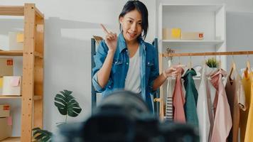 ung asiatisk dammodedesigner som använder mobiltelefon tar emot inköpsorder och visar kläder som spelar in video live streaming online med kamera. småföretagare, online marknadsföringskoncept. foto