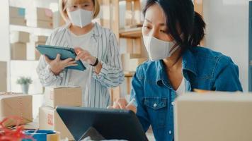unga asiatiska affärskvinnor bär ansiktsmask kontrollera produktens inköpsorder på lager och spara till surfplattans arbete på hemmakontoret. småföretagare, onlinemarknadsleverans, livsstilsfrilanskoncept foto