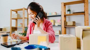 ung asiatisk affärskvinna som använder mobiltelefonsamtal som tar emot inköpsorder och kontrollerar produkten i lager, arbetar på hemmakontoret. småföretagare, onlinemarknadsleverans, livsstil frilansande koncept. foto