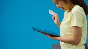 ung asiatisk dam med surfplatta och kreditbankkort med positivt uttryck, le brett, klädd i vardagskläder och stå isolerad på blå bakgrund. glad förtjusande glad kvinna jublar över framgång. foto