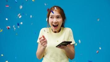 förvånad ung asiatisk dam som använder mobiltelefon med positivt uttryck, ler brett, klädd i avslappnad trasa under konfettiregn och firar på blå bakgrund. glad glad kvinna jublar över framgång. foto