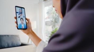 ung asiatisk muslimsk affärskvinna som använder smart telefonsamtal med kollega genom videochatt -brainstorm online -möte medan hon arbetar på distans hemifrån i vardagsrummet. social distansering, karantän för corona. foto