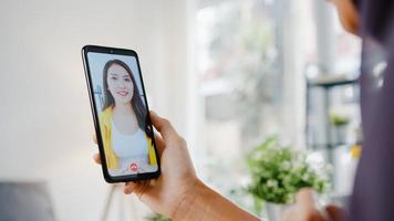 ung asiatisk muslimsk affärskvinna som använder smart telefon prata med en vän genom videochatt -brainstorm online -möte medan hon arbetar på distans hemifrån i vardagsrummet. social distansering, karantän för corona. foto