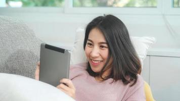 asiatisk kvinna som lyssnar på musik och använder surfplatta, kvinnan använder slappningstid liggande på hemmasoffan i vardagsrummet hemma. glad kvinnlig lyssnar musik med hörlurar koncept. foto