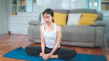 ung asiatisk kvinna som utövar yoga i vardagsrummet. attraktiv vacker kvinna som tränar för friska hemma. livsstil kvinna träning koncept. foto