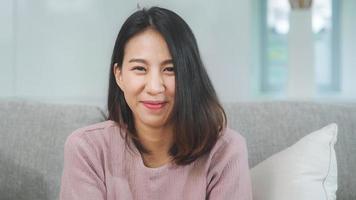 tonåring asiatisk kvinna som känner sig lycklig leende och ser till kameran medan du kopplar av i vardagsrummet hemma. livsstil vacker asiatisk ung kvinna med hjälp av koppla av hemma koncept. foto