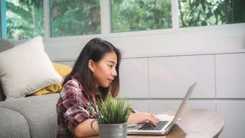 ung affärs frilans asiatisk kvinna som arbetar på bärbar dator som kontrollerar sociala medier medan hon ligger i soffan när hon kopplar av i vardagsrummet hemma. livsstil latin och spansktalande etnicitet kvinnor hemma koncept. foto
