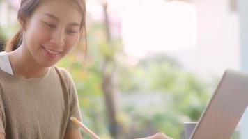 frilans asiatisk kvinna som arbetar hemma, affärskvinna som arbetar på bärbar dator sitter på bordet i trädgården på morgonen. livsstil kvinnor arbetar hemma koncept. foto